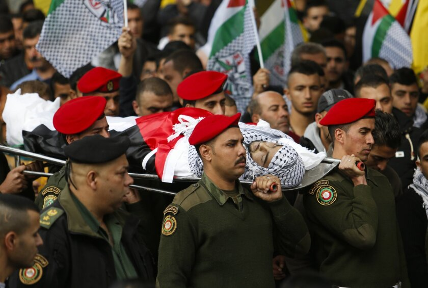 Palestinian security officers carry the body of 16-year-old Ibrahim Dawood during his funeral in the West Bank city of Ramallah, Thursday, Nov. 26, 2015. Ibrahim died of his wounds sustained during clashes with Israeli soldiers two weeks ago near Beit El settlement, on the northern entrance of Ramallah, in a statement for the Palestinian ministry of health. (AP Photo/Nasser Shiyoukhi)