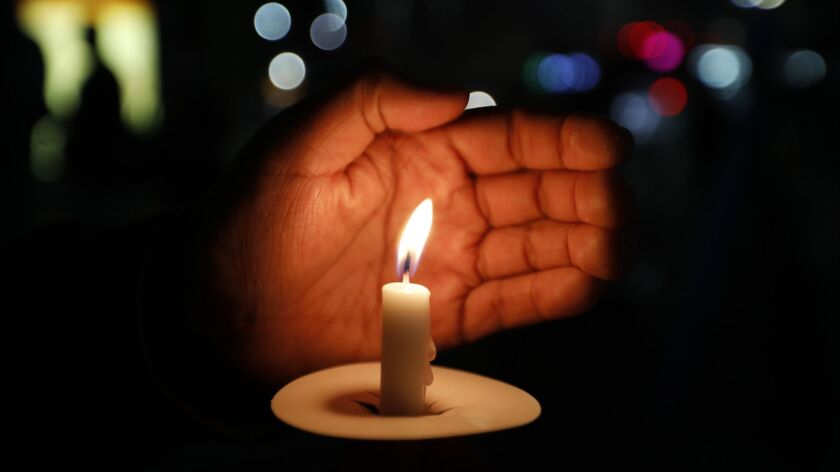 LOS ANGELES, CA AUGUST 31, 2018: Alan Antonio, 18, holds a candle during a vigil in the Koreatown