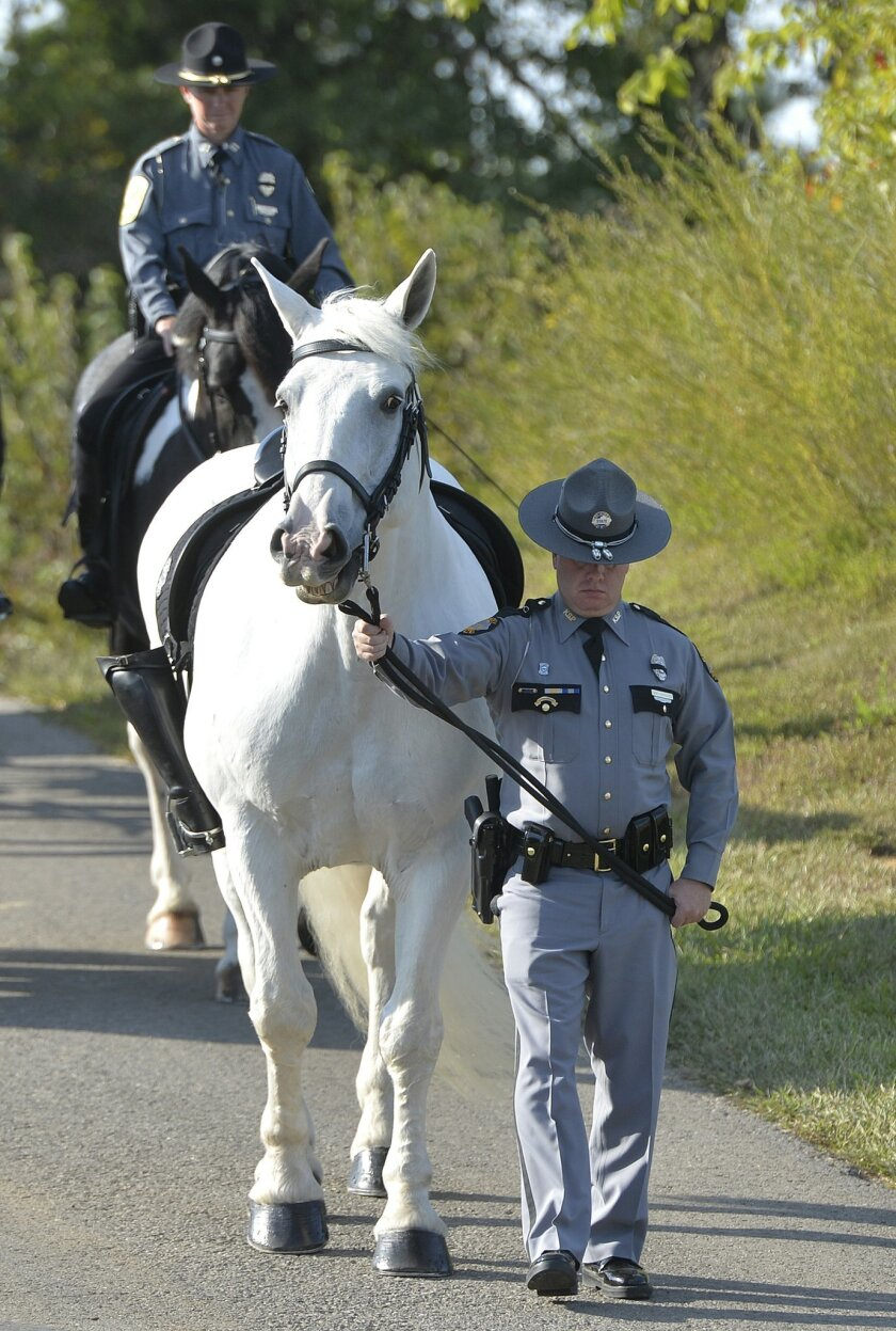A Kentucky State Trooper leads a riderless horse ahead of the caisson carrying the remains of slain Kentucky State Police Trooper Joseph Cameron Ponder to his services at the Kentucky Veterans Cemetery in Radcliff, Ky., Friday, Sept. 18, 2015. Ponder died Sunday night after being shot by a man he had stopped for speeding in western Kentucky. (AP Photo/Timothy D. Easley)