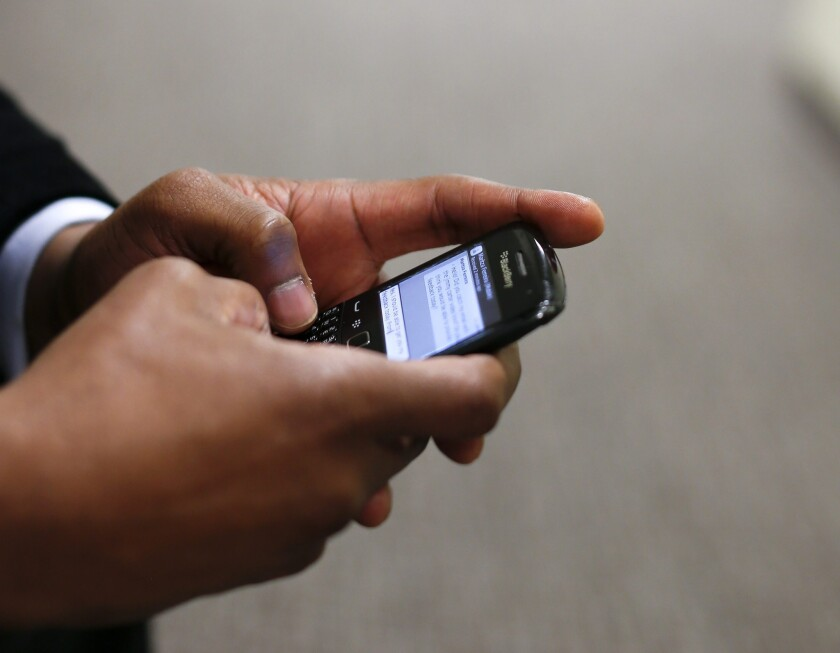 A man uses his Blackberry mobile device to write a text message in Atlanta in 2014. Unwanted calls and texts are the top consumer complaint to the Federal Communications Commission. The agency received 215,000 such complaints last year.