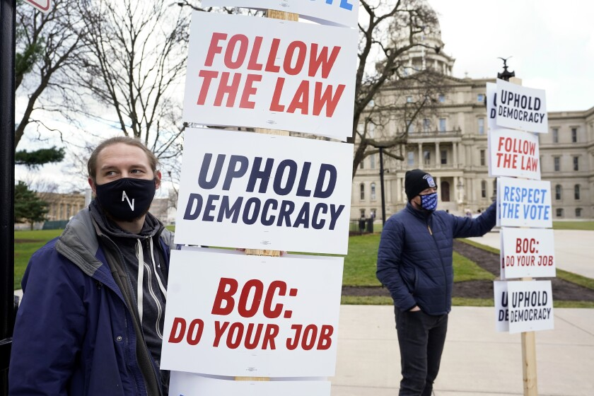 Joscha Weese, left, stands outside the Capitol building during a rally in Lansing, Mich.