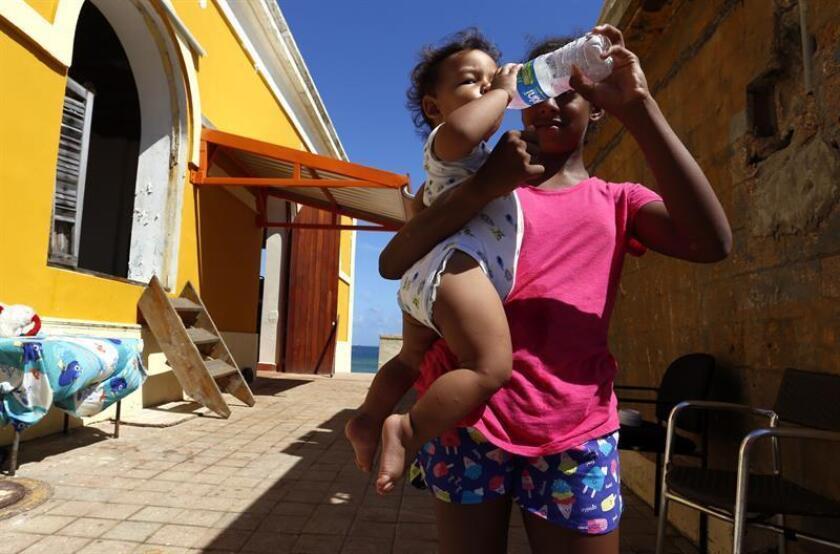 Una madre del barrio costero y popular La Perla da agua a un bebé en San Juan, Puerto Rico. EFE/Archivo