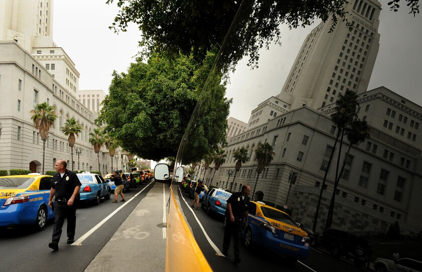 Taxis drive around City Hall in protest of the rideshare apps. The City Council may challenge a recent decision allowing the apps.