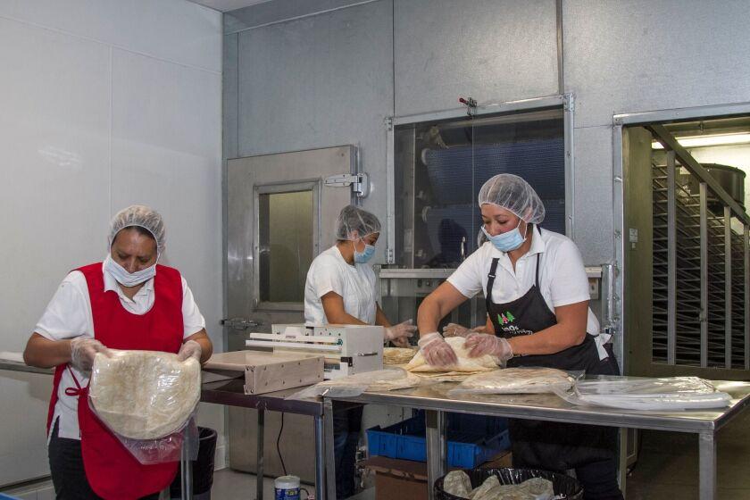 Empleadas empaquetan el producto recién salido del horno en la fábrica de la familia Alcázar.