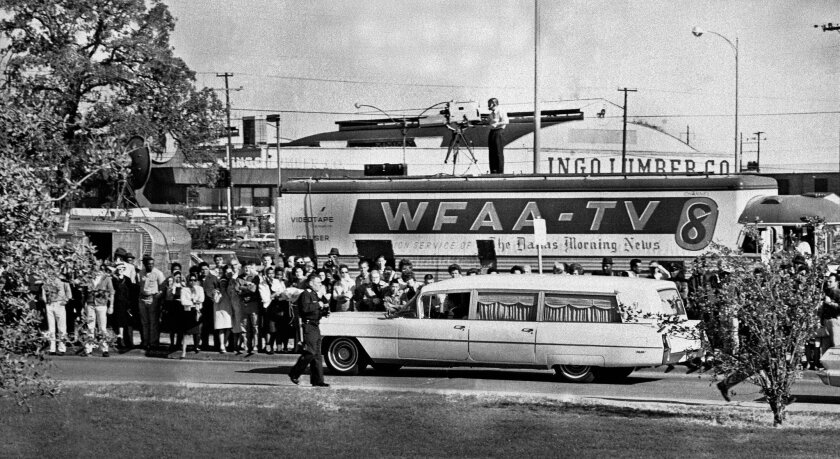 FILE - In this Nov. 22, 1963 file photo, people line the street as the hearse bearing the body of slain U.S. President John F. Kennedy leaves Parkland Hospital in Dallas, to be flown to Washington, D.C. (AP Photo/File)