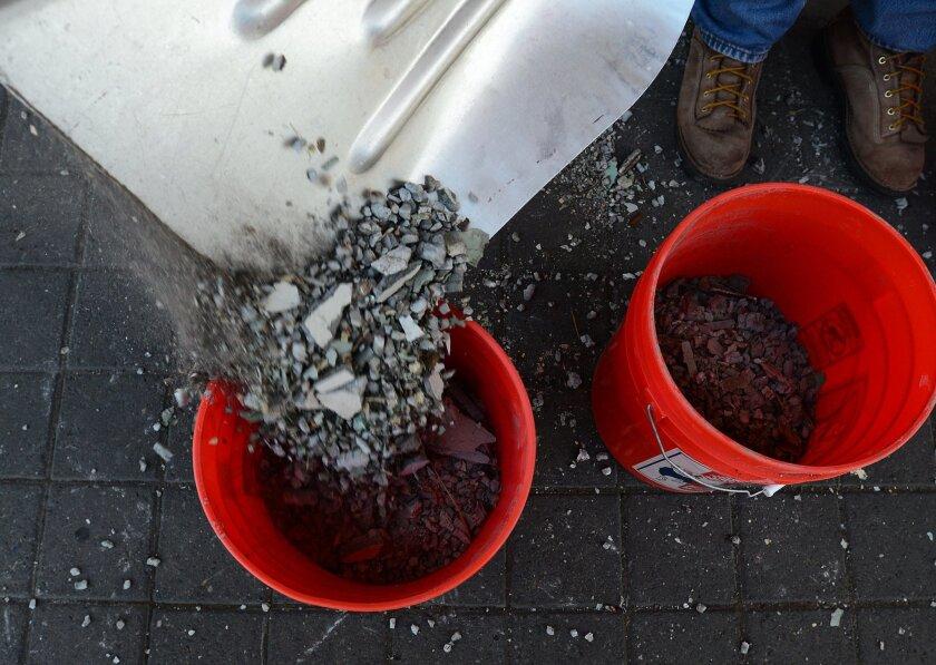 Corvallis resident Doug Eaton empties a shovel filled with debris into a bucket after taking down the front walls at the Whiteside Theatre in Corvallis, Ore., on Sunday, Aug., 16, 2015. (Godofredo Vasquez/Corvallis Gazette-Times via AP)