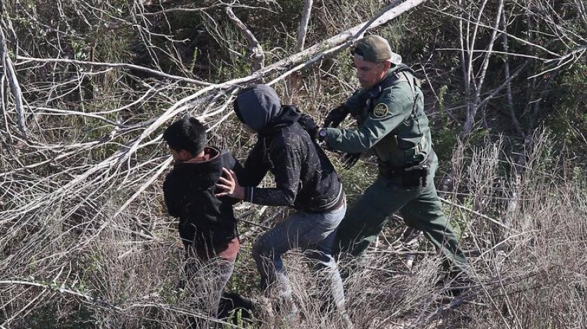 A Border Patrol agent detains undocumented juvenile immigrants in December.