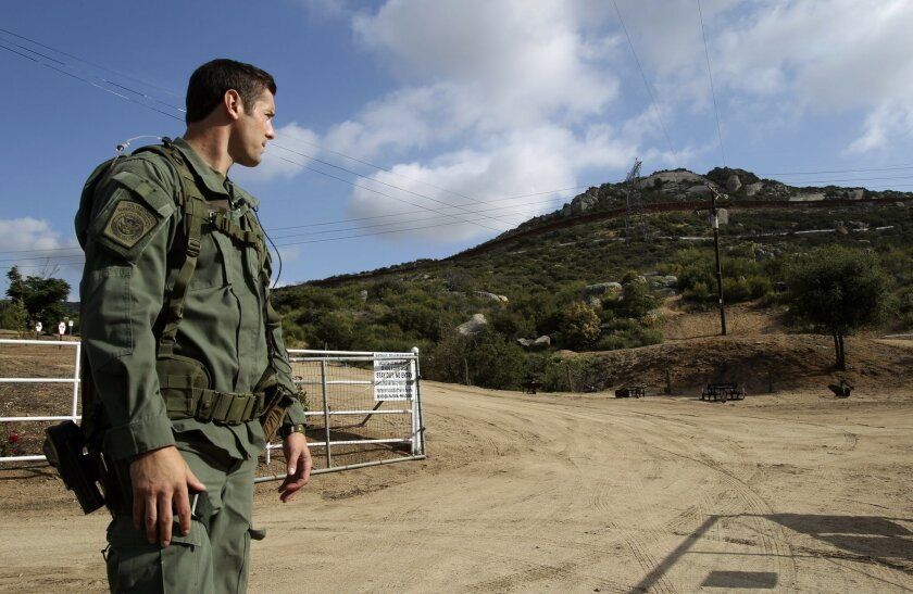 Border Patrol agent Cory Higbee, who is a member of the Border Patrol's elite search and rescue team called BORSTAR, looks toward the U.S./Mexican border fence east of Portrero on Wednesday.