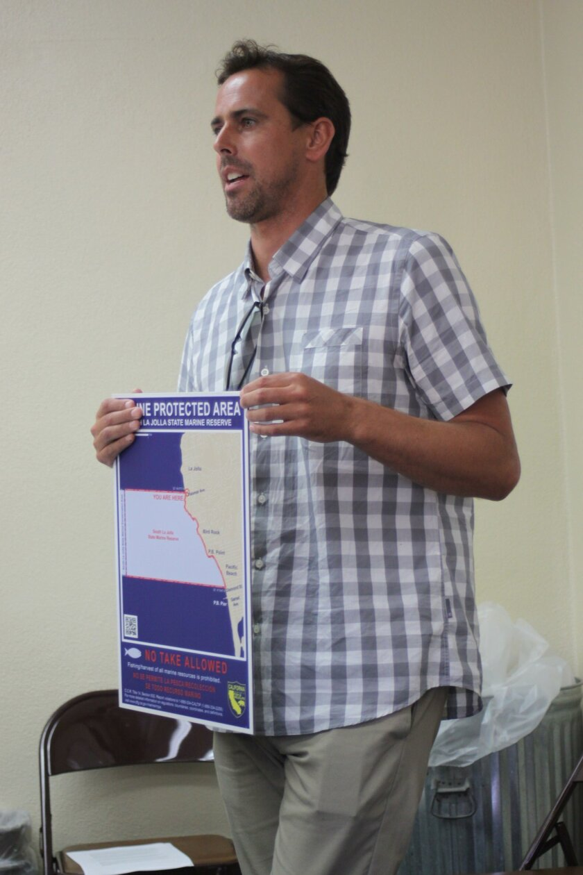 WildCoast Conservation Director Zach Plopper holds the proposed sign to be posted near the entrance of the Marine Protected Area at La Jolla Cove.