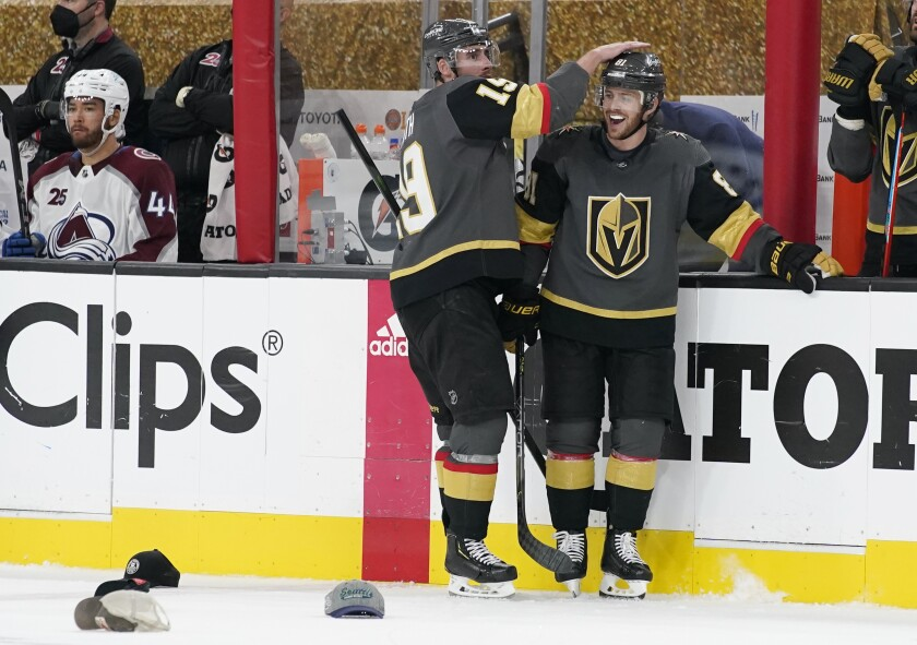 Vegas Golden Knights right wing Reilly Smith (19) celebrates after Vegas Golden Knights center Jonathan Marchessault, right, scored his third goal against the Colorado Avalanche during the third period in Game 4 of an NHL hockey Stanley Cup second-round playoff series Sunday, June 6, 2021, in Las Vegas. (AP Photo/John Locher)