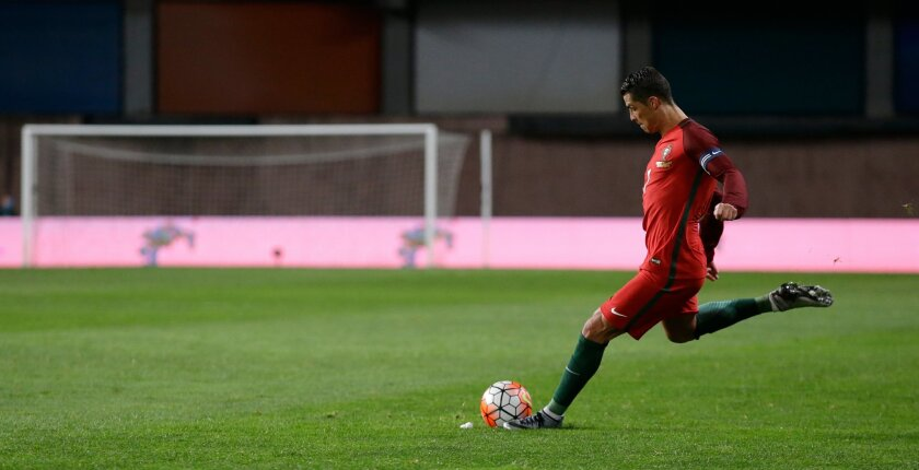 FILE -  In this Friday, March 25 2016 file photo, Portugal's Cristiano Ronaldo shoots a free kick during a friendly soccer match between Portugal and Bulgaria in Leiria, Portugal. For some just reaching the European Championship is enough. However, from the players to coaches and referees to admini