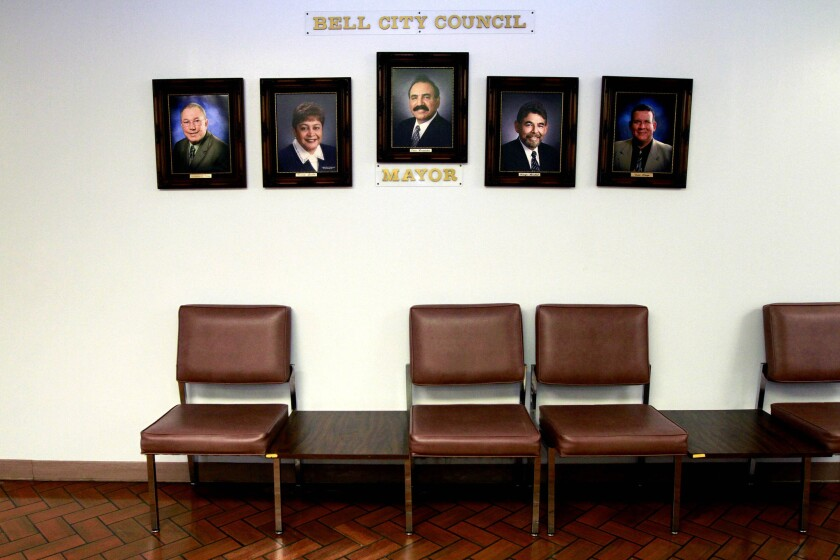 Photos of City Council member Lorenzo S. Velez, Vice Mayor Teresa Jacobo, City of Bell Mayor Oscar Hernandez, City Council member George Mirabal, and City Council member Luis Artiga hang inside the Bell City Hall building.