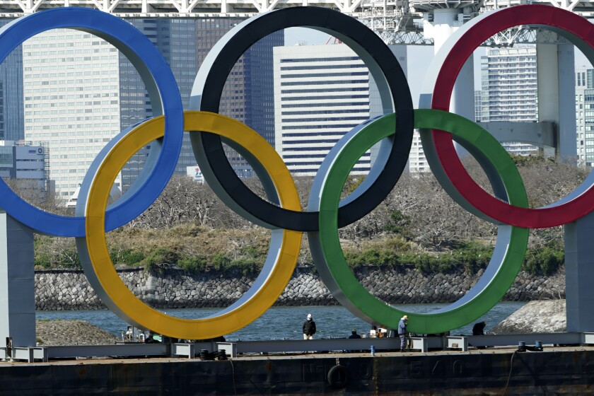 FILE - In this March 24, 2020, file photo, workers stand at the bottom of the Olympic rings at Tokyo's Odaiba district. Just two months after the unprecedented postponement. Chief Executive Toshiro Muto was asked Thursday, May 28, 2020 about progress rescheduling next year's Tokyo Olympics. (AP Photo/Eugene Hoshiko, File)