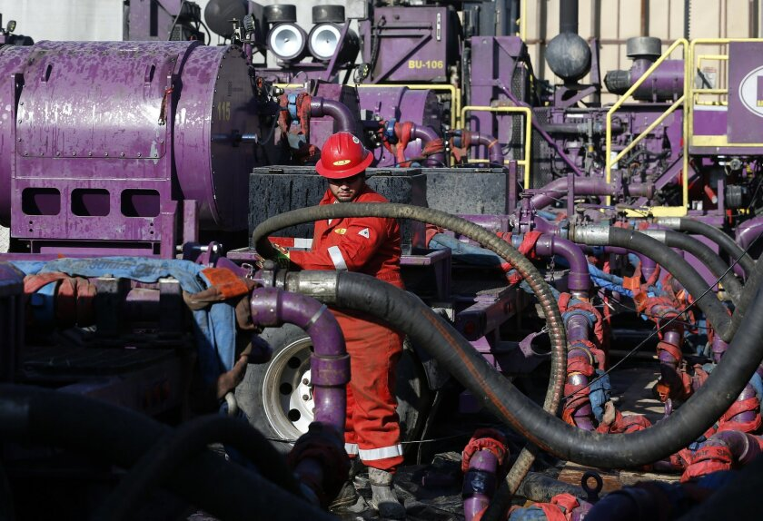 FILE - In this March 25, 2014 file photo, a worker adjusts hoses during a hydraulic fracturing operation at a gas well, near Mead, Colorado. During EPA hearings on methane in Denver Wednesday, Sept. 23, 2015, an energy industry representative told the Environmental Protection Agency that over-regulating methane emissions could discourage the use of environment-friendly natural gas. However, a former Colorado air quality official countered that such controls would be a cost-effective way to fight climate change. (AP Photo/Brennan Linsley, file)