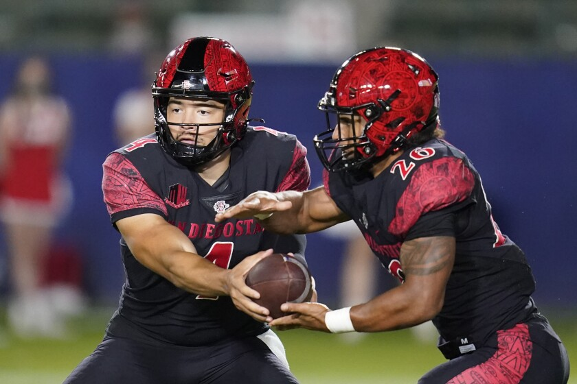 San Diego State quarterback Jordon Brookshire hands off to running back Kaegun Williams during game against New Mexico.