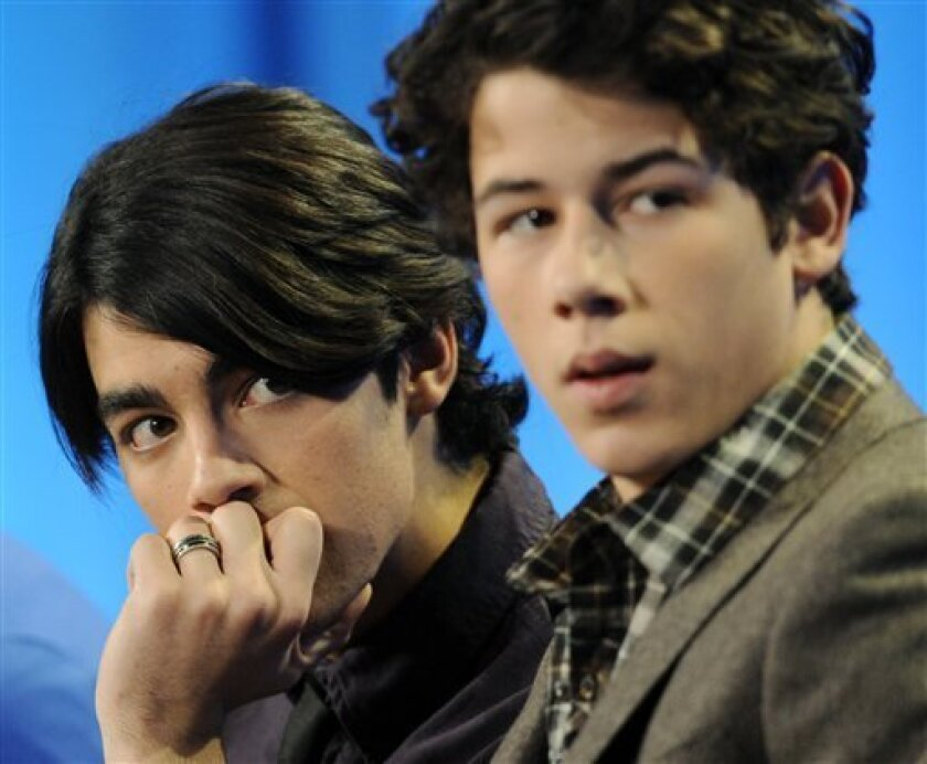 "Joe Jonas, left, and brother Nick Jonas, co-stars with their brother Kevin in the Disney Channel series ""JONAS,"" listen to remarks during a panel discussion at the Television Critics Association Winter Press Tour  in Los Angeles, Friday, Jan. 16, 2009. (AP Photo/Chris Pizzello)"
