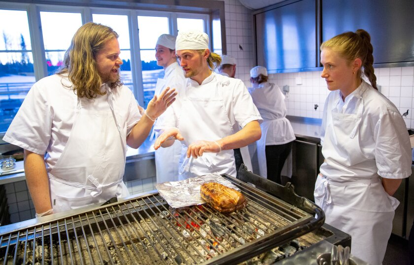 Head chef Magnus Nilsson talks with his staff while preparing a saddle of veal over an open fire at
