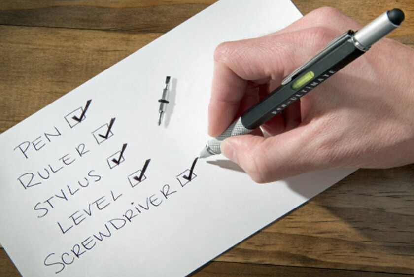 A hand holding a pen over a checklist that says pen, ruler, stylus, level, screwdriver.
