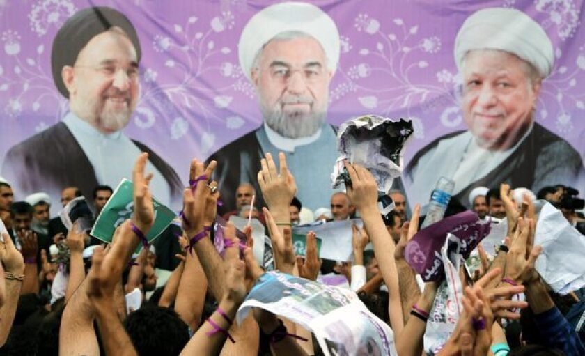 Supporters of late-surging Iranian presidential candidate Hassan Rowhani display their backing with purple ribbons and scarves, borrowing a color signature from the reformist Green Movement that was suppressed after the 2009 election. On the election banner backdrop, Rowhani is flanked by former presidents Ali Akbar Hashemi Rafsanjani, left, and Mohammad Khatami.