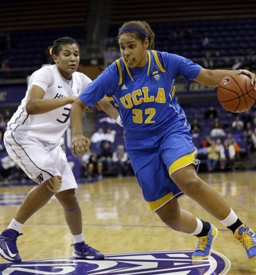 UCLA's Alyssia Brewer (32) drives past Washington's Talia Walton in the second half of an NCAA college basketball game Friday, Feb. 8, 2013, in Seattle. UCLA won 65-61. (AP Photo/Elaine Thompson)