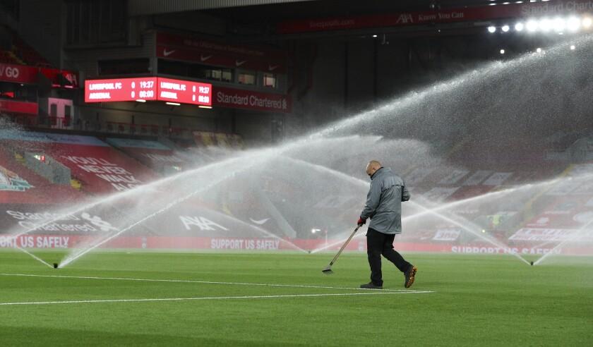 Un empleado da mantenimiento a la cancha previo al partido entre Liverpool y Arsenal por la Copa de la Liga inglesa