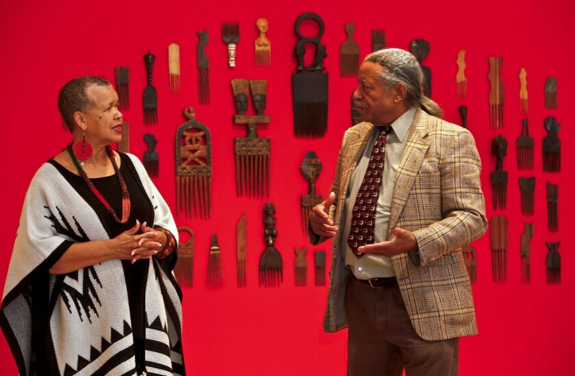 """Curator Starla Lewis, left, put together the exhibit """"The History and the Hair Story: 400 Years Without a Comb"""" using items from the collection of Willie Morrow, right."""