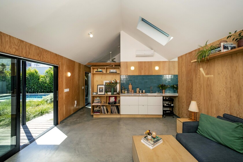 The interior of the ADU, featuring plywood walls and views of the garden and saltwater pool.
