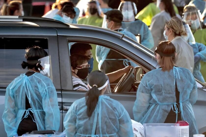 Una familia detiene la marcha de su vehículo en un centro de pruebas gratuitas de COVID-19
