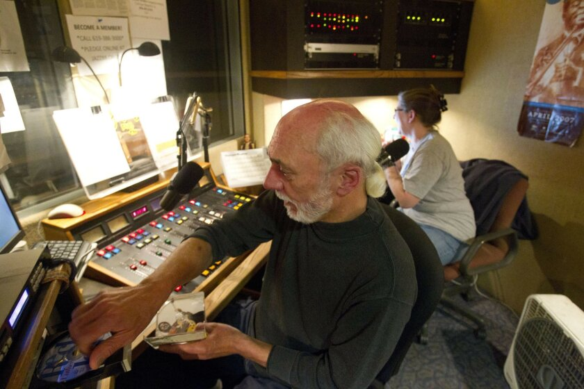 """Ted """"T"""" Herring, the host of KSDS Jazz 88's weekly, four-hour Saturday night blues show, """"Every Shade of Blue,"""" cues music for his program. Claudia Russell, KSDS's music director (right), joins him to encourage listener support.  Herring, who broadcasts under the name T, this month celebrated his 3"""