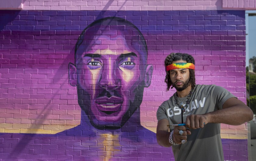 """Artist Joshua """"Prophet Josh"""" McCadney stands by one of two Kobe murals he created on Melrose Avenue."""