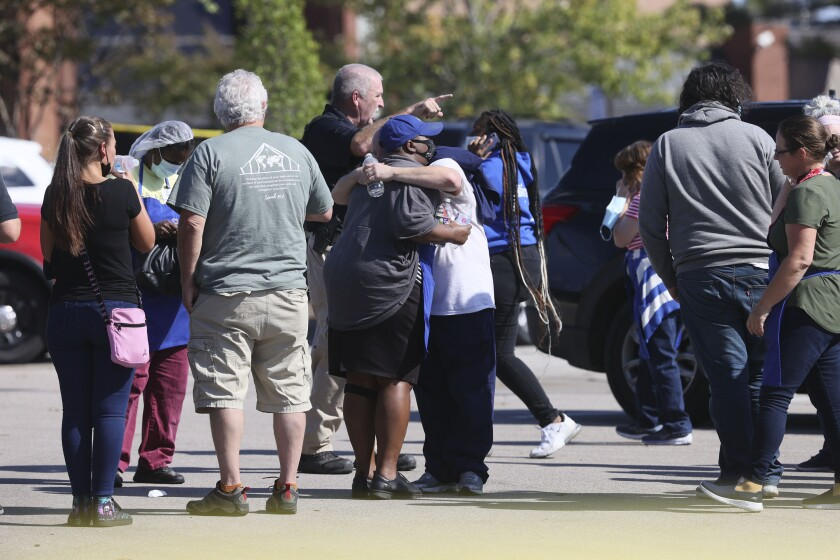 People embrace as police respond to the scene of a shooting