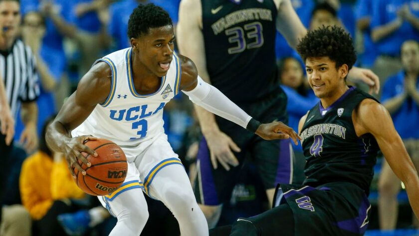 UCLA guard Aaron Holiday and Washington guard Matisse Thybulle in action.