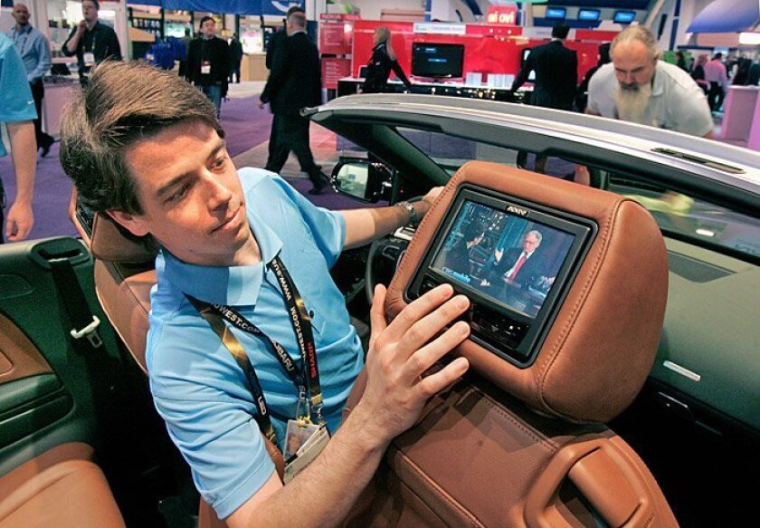 Qualcomm engineer Christopher Gould, in an Audi Quattro convertible with rear-facing monitors, watched broadcast television with Qualcomm's Flo TV technology at the CES in Las Vegas.