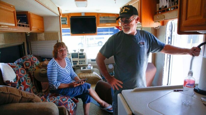 Ken Settles and his wife, Dee Settles relax in their motorhome parked at the Red Cross evacuation ce
