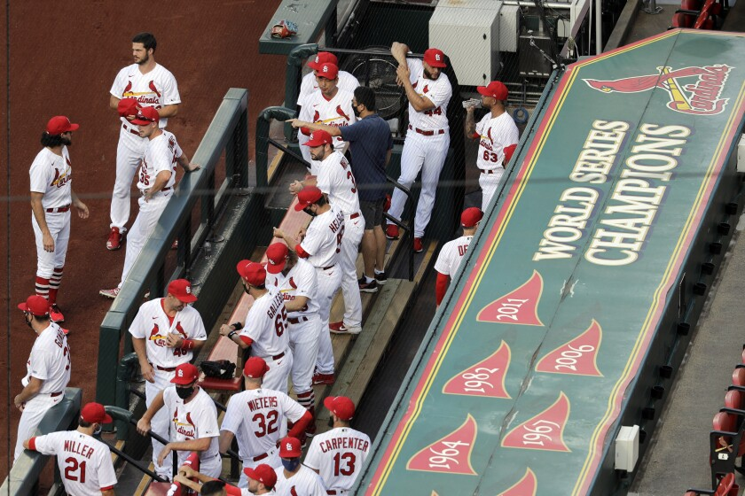 FILE - In this July 24, 2020, file photo, members of the St. Louis Cardinals wait to be introduced before the start of a baseball game against the Pittsburgh Pirates in St. Louis. The Cardinals 4-game series against the Detroit Tigers was postponed Monday, Aug. 3, 2020, after more Cardinals players and staff staffers test positive for COVD-19. The series was to have been played in Detroit from Tuesday through Thursday. (AP Photo/Jeff Roberson, File)