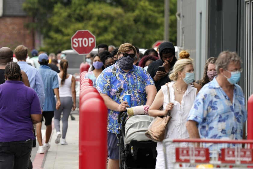 People line up to enter retail chain Costco to buy provisions in New Orleans on Sunday.