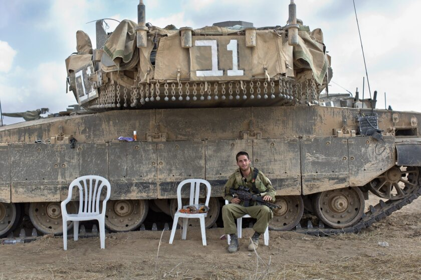 An Israeli soldier sits next to a Merkava tank in a staging area in southern Israel along the border with the Gaza Strip on Tuesday.