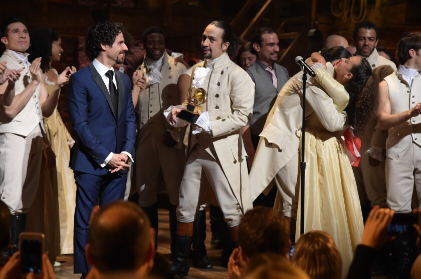 "Music director Alex Lacamoire, left, and actor-composer Lin-Manuel Miranda and the cast of ""Hamilton"" celebrate on stage after receiving as Grammy award"