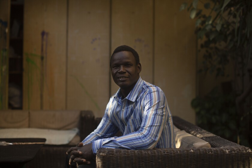 """In this Nov. 27, 2019 photo, Patrice Gaudensio, a refugee artist from South Sudan poses for a portrait during an exhibition titled """"Beyond Borders,"""" featuring work by refugee artists, at Art Cafe in Cairo, Egypt. Gaudensio said he and his wife have experienced racism and discrimination several times in Cairo streets. Hundreds of thousands of sub-Saharan African migrants call Cairo their temporary home. Many have fled deadly violence or dire poverty at home only to face racist harassment, violence and rape in the megacity of some 20 million people. (AP Photo/Maya Alleruzzo)"""