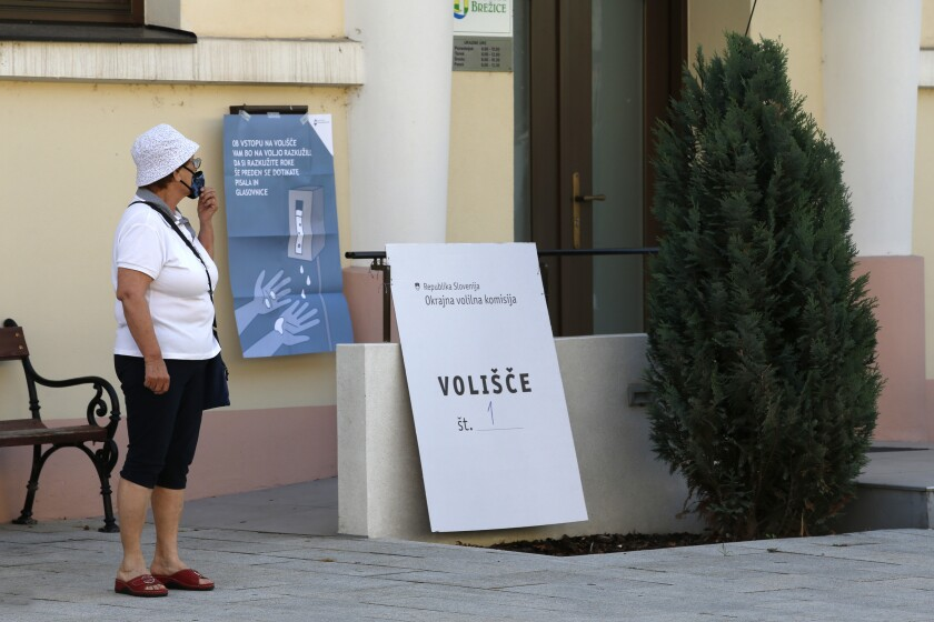 A voter stands in front of a polling station in Brezice, Slovenia, Sunday, July 11, 2021. Slovenians voted in a referendum on changes to the country's waters management law that is seen as a test for the government of right-wing Prime Minister Janez Jansa. Jansa's government approved the amendments in March but ecologists have pushed through the referendum saying they threaten the environment by paving the way for construction by the sea, rivers and lakes. (AP Photo)