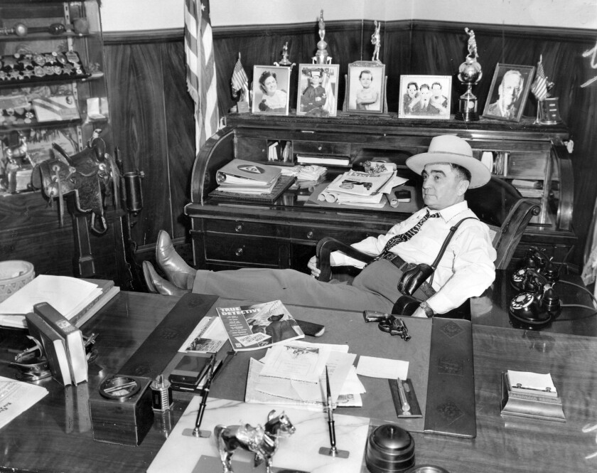 A 1943 file photo of Sheriff Eugene Biscailuz in his office with his feet up and a revolver on his desk.