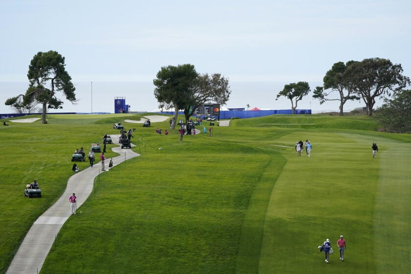 FILE - In this Jan. 31, 2021, file photo, Jon Rahm, lower right, of Spain, walks down with 13th fairway with his caddie, Adam Hayes, on the South Course during the final round of the Farmers Insurance Open golf tournament at Torrey Pines in San Diego. Rahm will return from self-isolation for a positive COVID-19 test in time for the U.S. Open at Torrey Pines on June 17-20. (AP Photo/Gregory Bull, File)