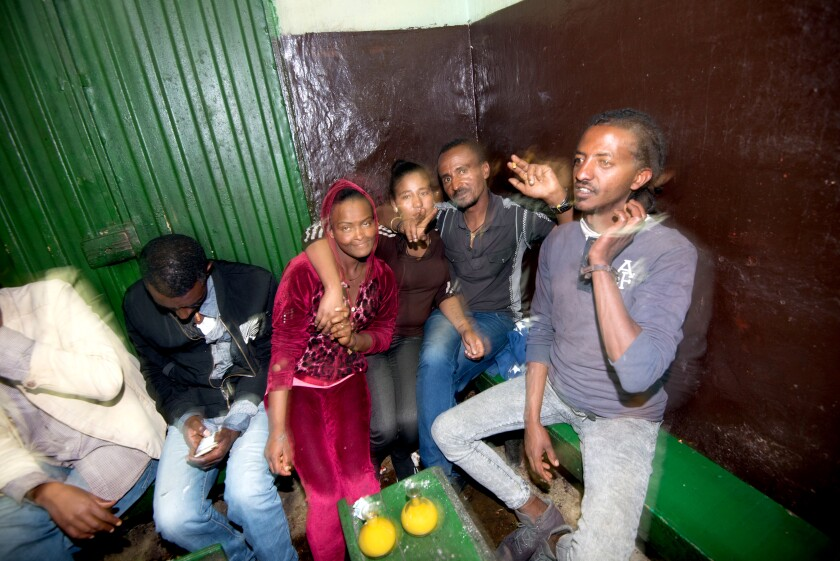 Customers enjoying tej bet and one another's company at a bar in Addis Ababa, Ethiopia