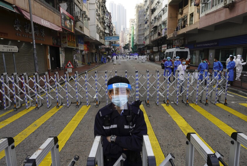 A police officer stands guard in a street in Hong Kong with roadblocks and people in PPE nearby.