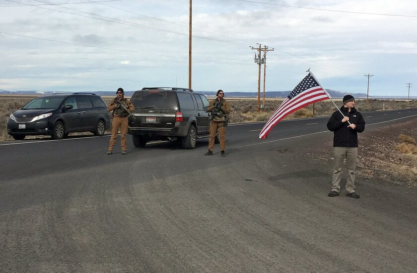 Armed law enforcement officers stand near a closed highway about 4 miles outside of the Malheur National Wildlife Refuge in Burns, Ore, after the last four occupiers of the national nature preserve surrendered on Thursday, Feb. 11, 2016. The holdouts were the last remnants of a larger group that se