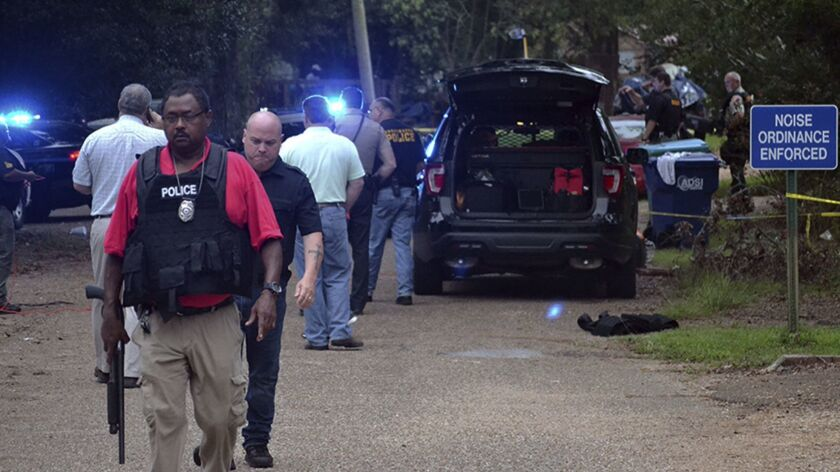 Law enforcement agents secure the scene of a shooting in Brookhaven, Miss., where two police officer