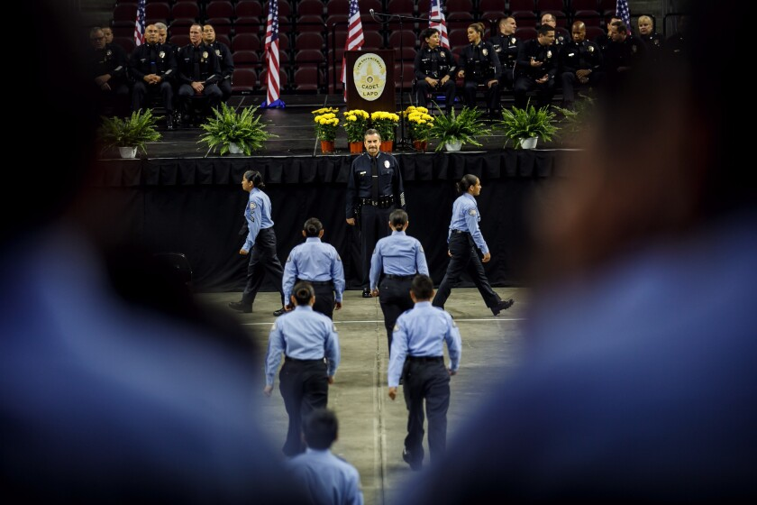 Cadets file past Los Angeles Police Chief Charlie Beck for inspection before their graduation ceremony at USC's Galen Center in June.