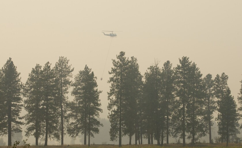 A firefighting helicopter returns to base while fighting the Carlton Complex fires near Twisp, Wash.