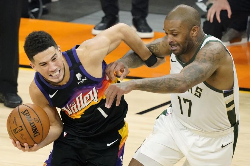Devin Booker, izquierda, de los Suns de Phoenix