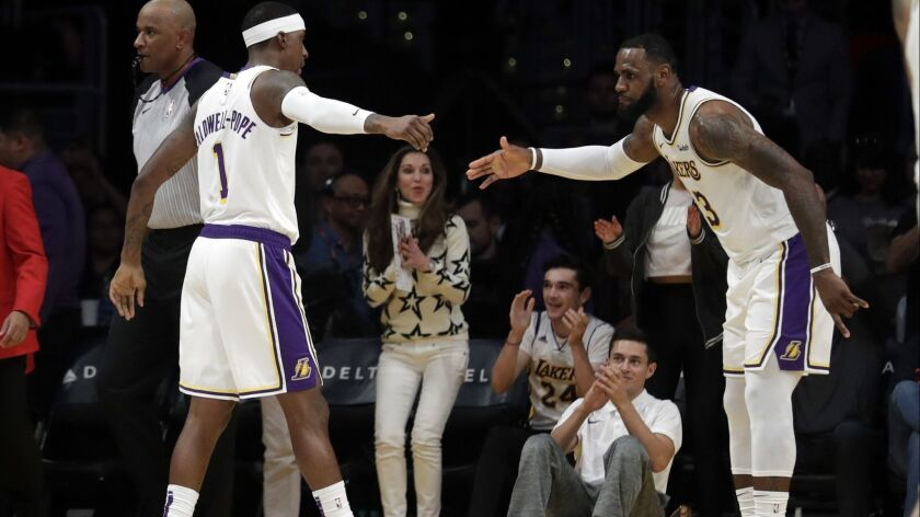 Lakers' Kentavious Caldwell-Pope (1) shakes hands with LeBron James during the first half on Sunday.